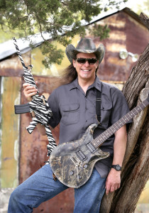 PHOTO COURTESY OF MICHAEL IVES Toting a guitar covered with camouflage pattern and a zebra-striped semi-automatic assault rifle, Ted Nugent is ready for an assault on the outdoors.